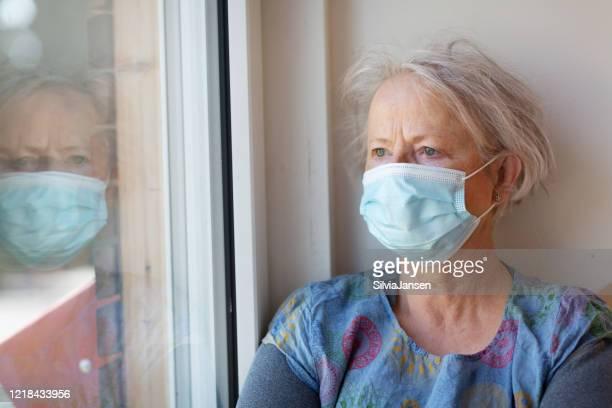 äldre kvinna som tittar ut ur den under karantän orsaken till covid-19 - munskydd ensam bildbanksfoton och bilder