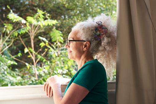 senior woman looking out of window - gettyimageskorea