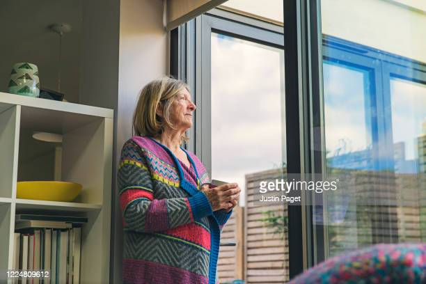 senior woman looking out of window with a cuppa - illness prevention stock pictures, royalty-free photos & images