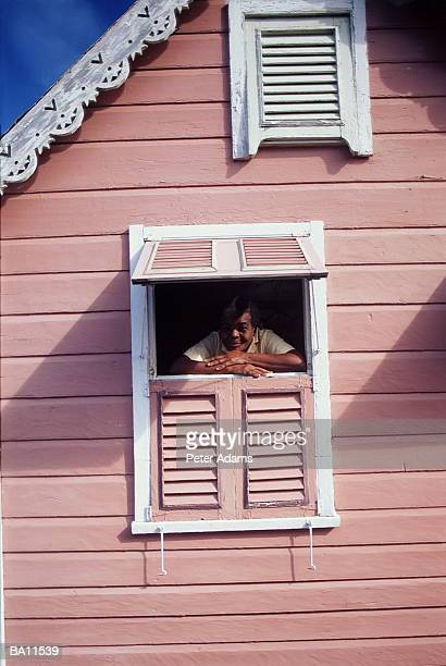 senior woman looking out window of pink house - trinidad and tobago stock pictures, royalty-free photos & images