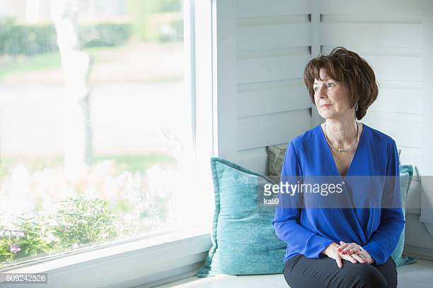 Senior woman looking out window with serious face