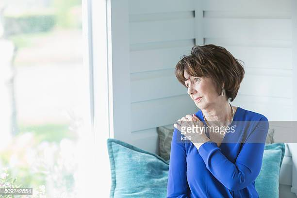 senior woman looking out window with serious face - hand on shoulder stock pictures, royalty-free photos & images