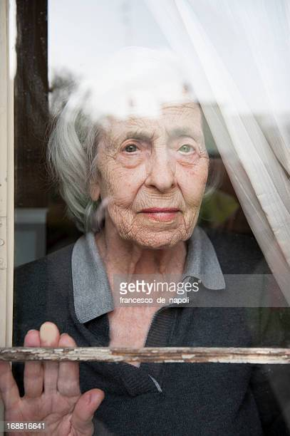 Senior woman looking through a window looking lonely