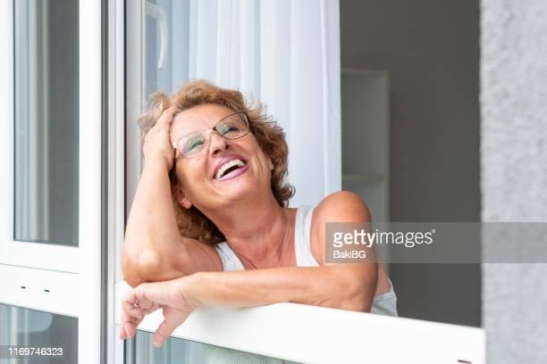 彼女のアパートの窓から見ているシニア女性 - オードフランス地域圏 ストックフォトと画像