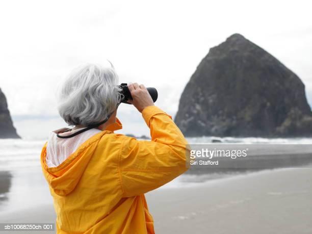 Senior woman looking through binoculars on beach