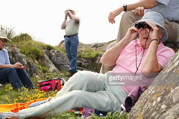 Senior woman looking through binoculars on family picnic