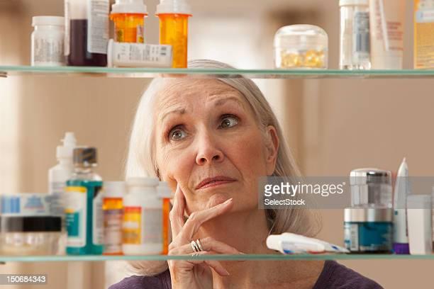 Senior Frau Blick durchs Badezimmerschrank