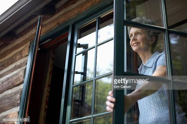 Senior woman looking through open window