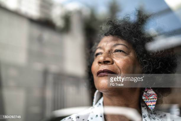 senior woman looking through the window at home - brazil stock pictures, royalty-free photos & images