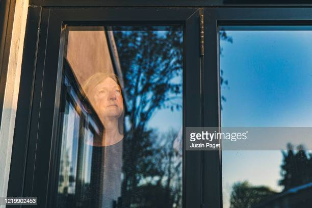 senior woman looking through window - quarantine stock pictures, royalty-free photos & images