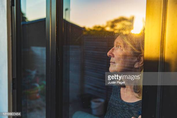senior woman looking through window - hope stock pictures, royalty-free photos & images