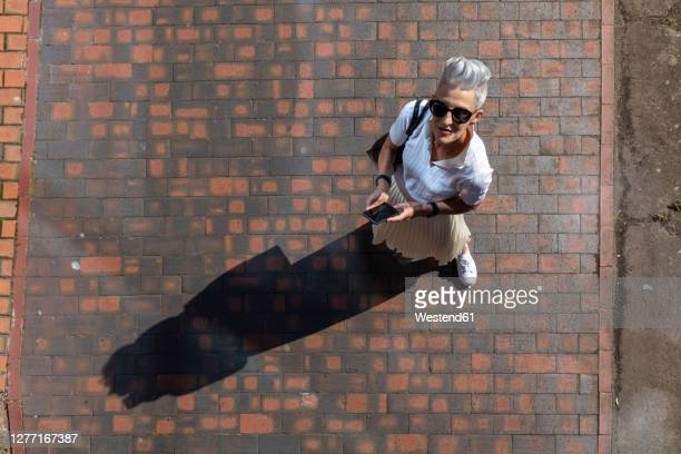 senior woman looking up while standing with smart phone on footpath - elevated view stock pictures, royalty-free photos & images