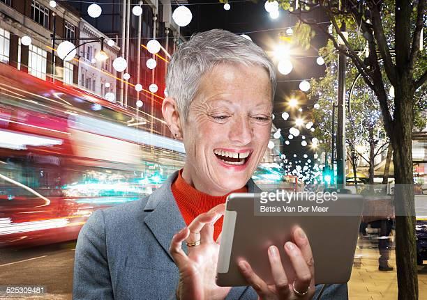 senior woman looks at digital device in street.