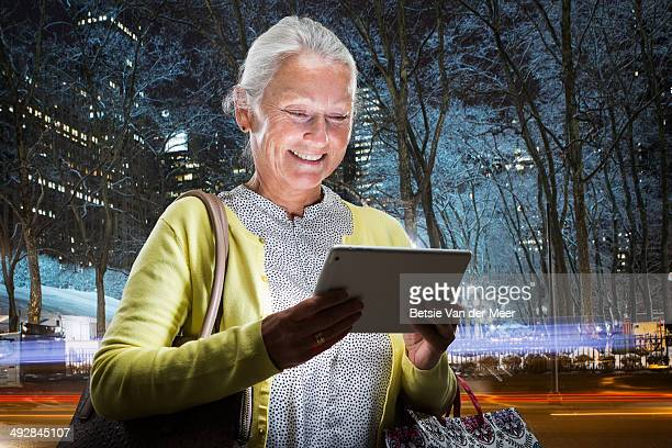 Senior woman looks at digital tablet in city.
