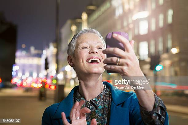 Senior woman looks at phone in city at night.
