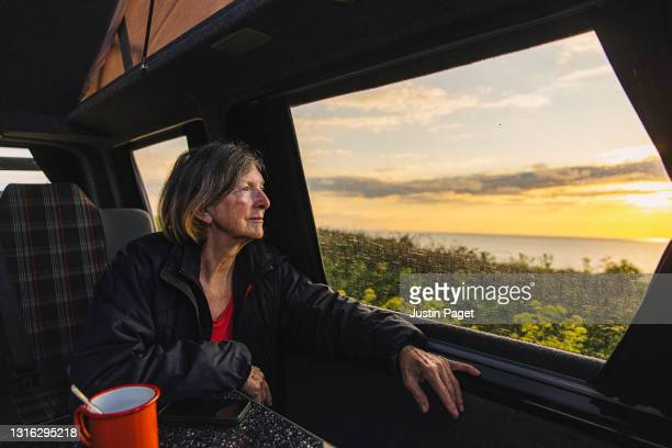 a senior woman looks at the view of the sea at sunset from her campervan - tranquil scene stock pictures, royalty-free photos & images