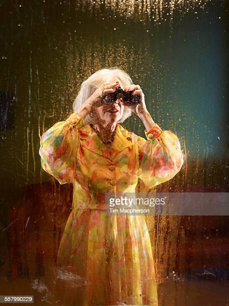 senior woman looks through binoculars - binoculars stock pictures, royalty-free photos & images