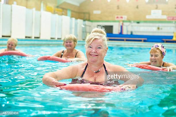 senior woman looks to camera at water aerobics