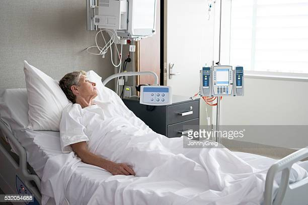 Senior woman lying in hospital bed looking away