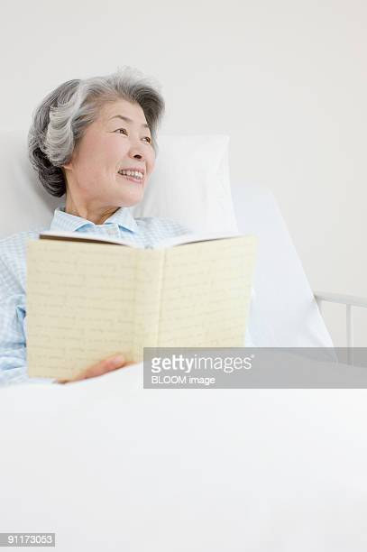 Senior woman lying in hospital bed, reading book