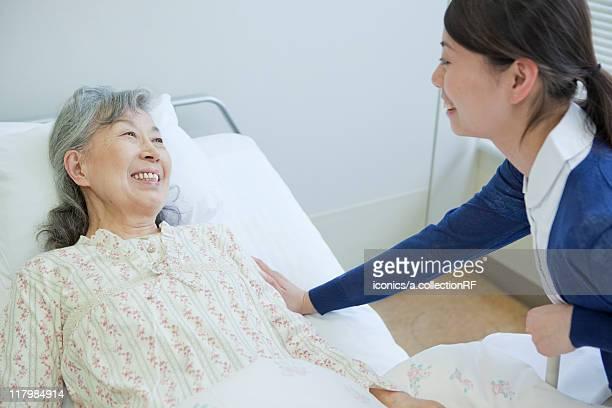 Senior woman lying on bed talking to nurse, Kanagawa Prefecture, Honshu, Japan