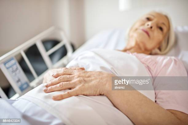 senior woman lying on hospital bed - letto foto e immagini stock