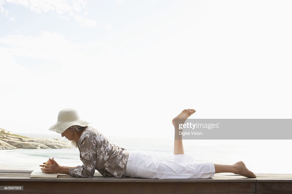 Senior Woman Lying on Wooden Decking on the Coast and Reading a Book : Stock Photo