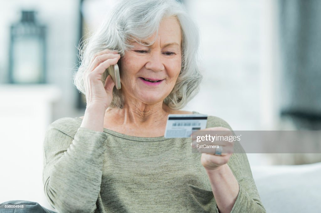 Senior Woman Making a Call With Credit Card : Stock Photo