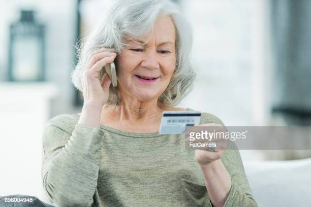 senior woman making a call with credit card - fraud stock pictures, royalty-free photos & images