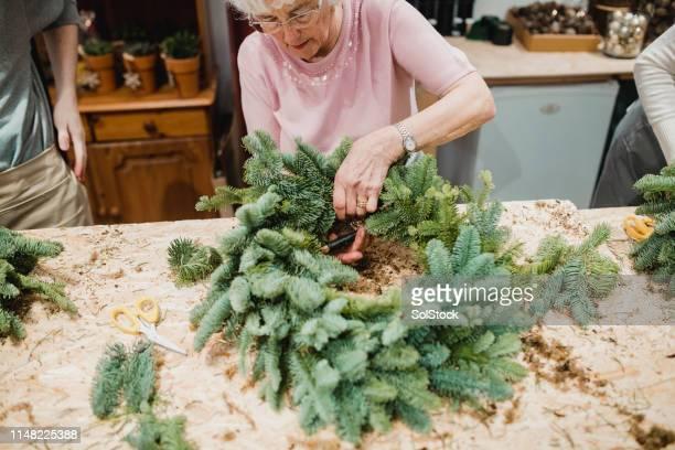 senior woman making a christmas wreath - avvento foto e immagini stock