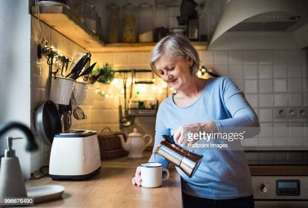 Senior woman making coffee in the kitchen at home.