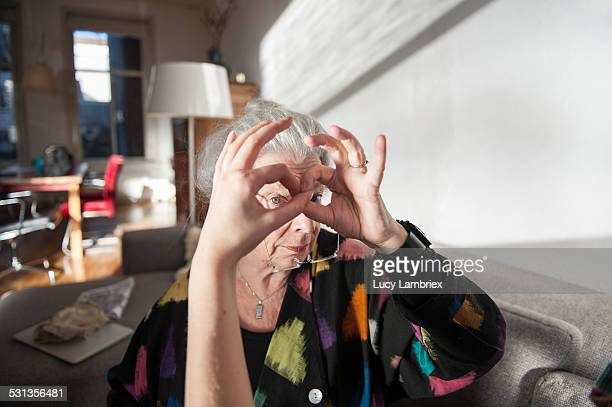 Senior woman making glasses with hands