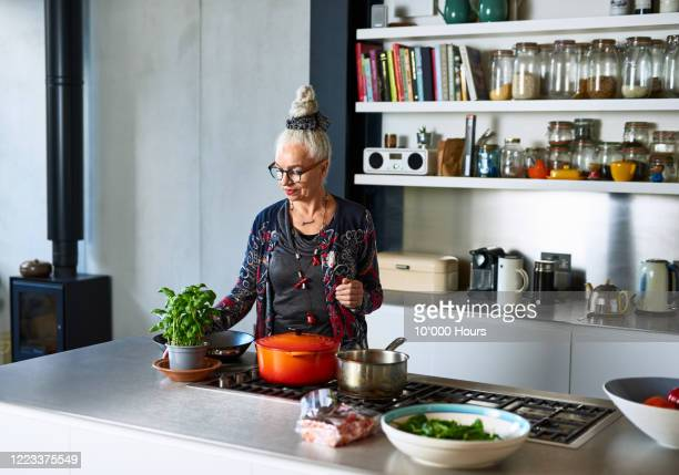 senior woman making meal at home with fresh ingredients - cooking stock pictures, royalty-free photos & images