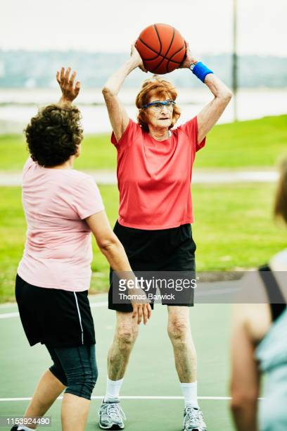 senior woman making pass during early morning basketball game with friends - disruptaging stock photos and pictures