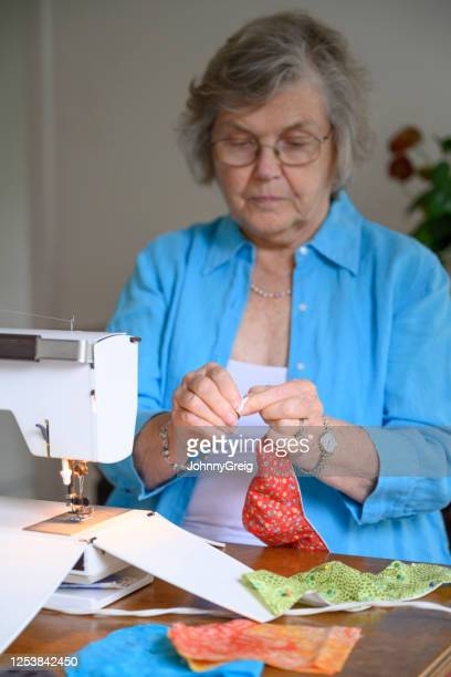 senior woman making protective face mask at home - craft stock pictures, royalty-free photos & images