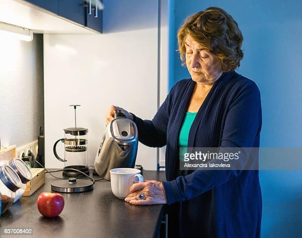 Senior woman making tea in her kitchen