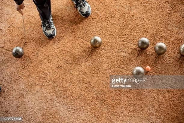 Senior Woman Marking Where Bocce Ball Has Stopped