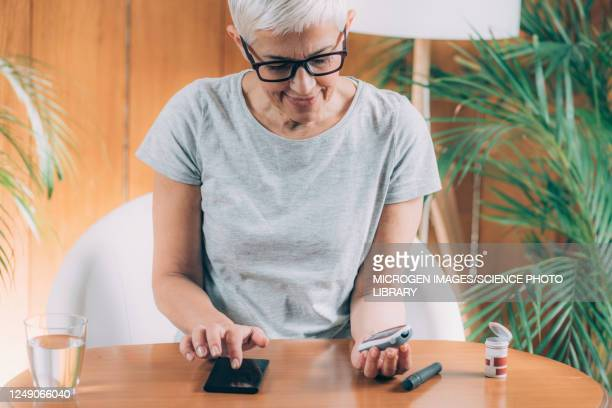 senior woman measuring glucose levels - diabetes stock pictures, royalty-free photos & images