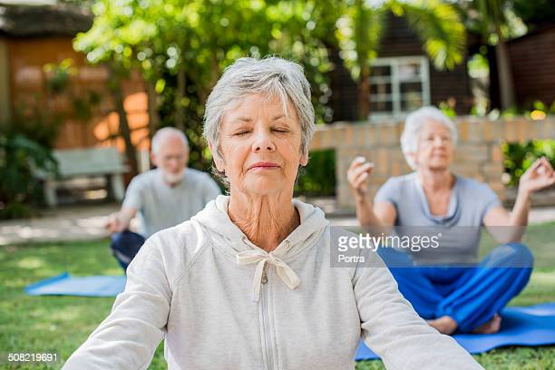 Senior woman mediating with friends in park