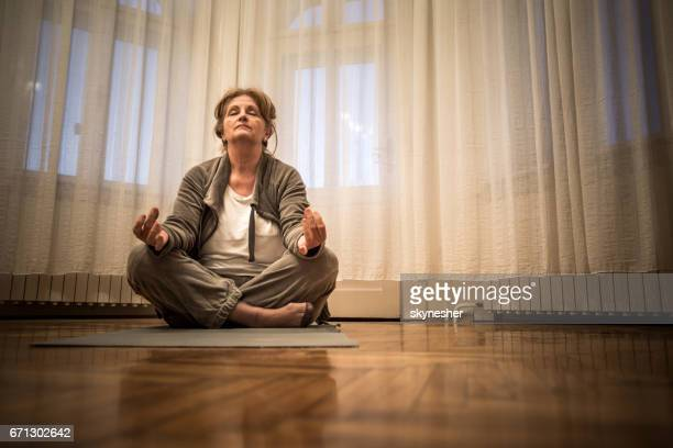 senior woman meditating in lotus position at home. - one senior woman only stock pictures, royalty-free photos & images