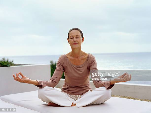 senior woman meditating in the lotus position with the sea in the background - cushion stock photos and pictures