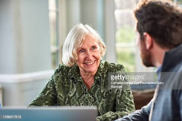 senior woman meeting with financial consultant at home - photography stock pictures, royalty-free photos & images