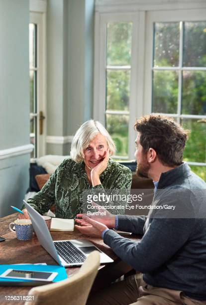 senior woman meeting with financial consultant at home - planning stock pictures, royalty-free photos & images