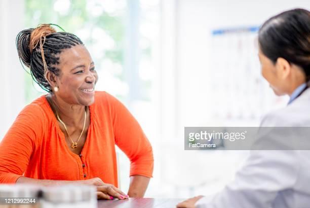彼女の医者のストック写真とシニアウーマンミーティング - オレンジ色のシャツ ストックフォトと画像