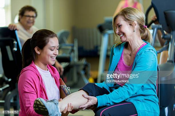senior woman meets with physical therapist - knees together stock photos and pictures