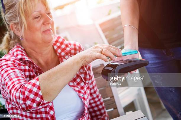 Senior woman Mobile payment in cafe