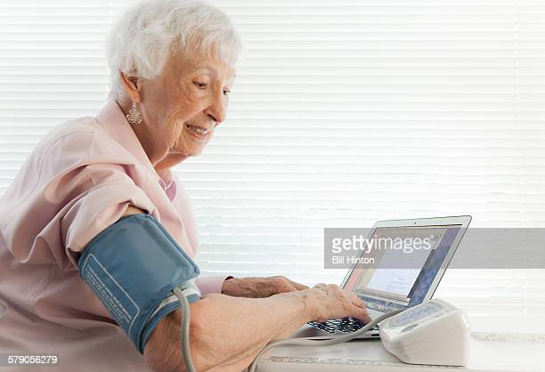 Senior woman monitoring blood pressure on line at home