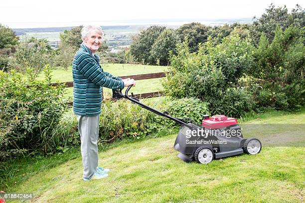 senior woman mowing grass