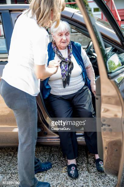 Senior Woman Needs Help to Come Out of Car