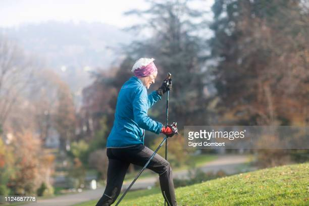 senior woman nordic walking in park - sigrid gombert stock pictures, royalty-free photos & images